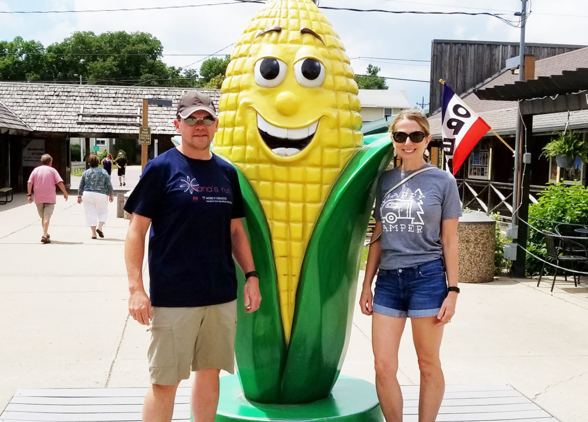 Standing next to a giant ear of corn
